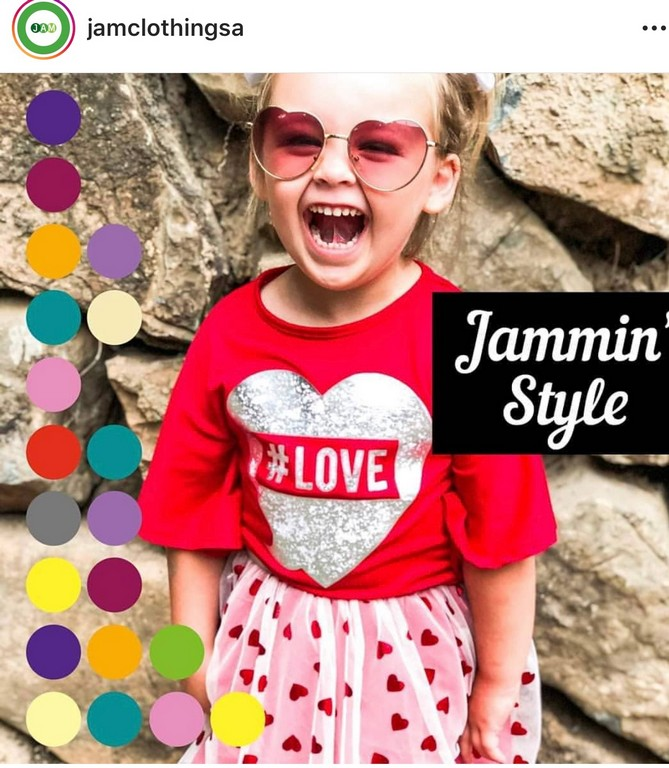 little girl laughing wearing red and white shirt and skirt from jam clothing with sunglasses