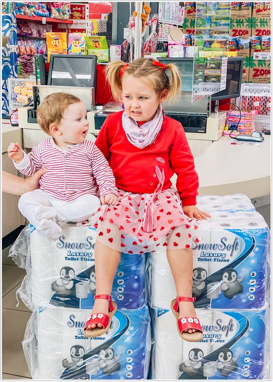 baby boy and girl sitting on bale of toilet paper in west pack lifestyle store part of the west pack toilet paper challenge