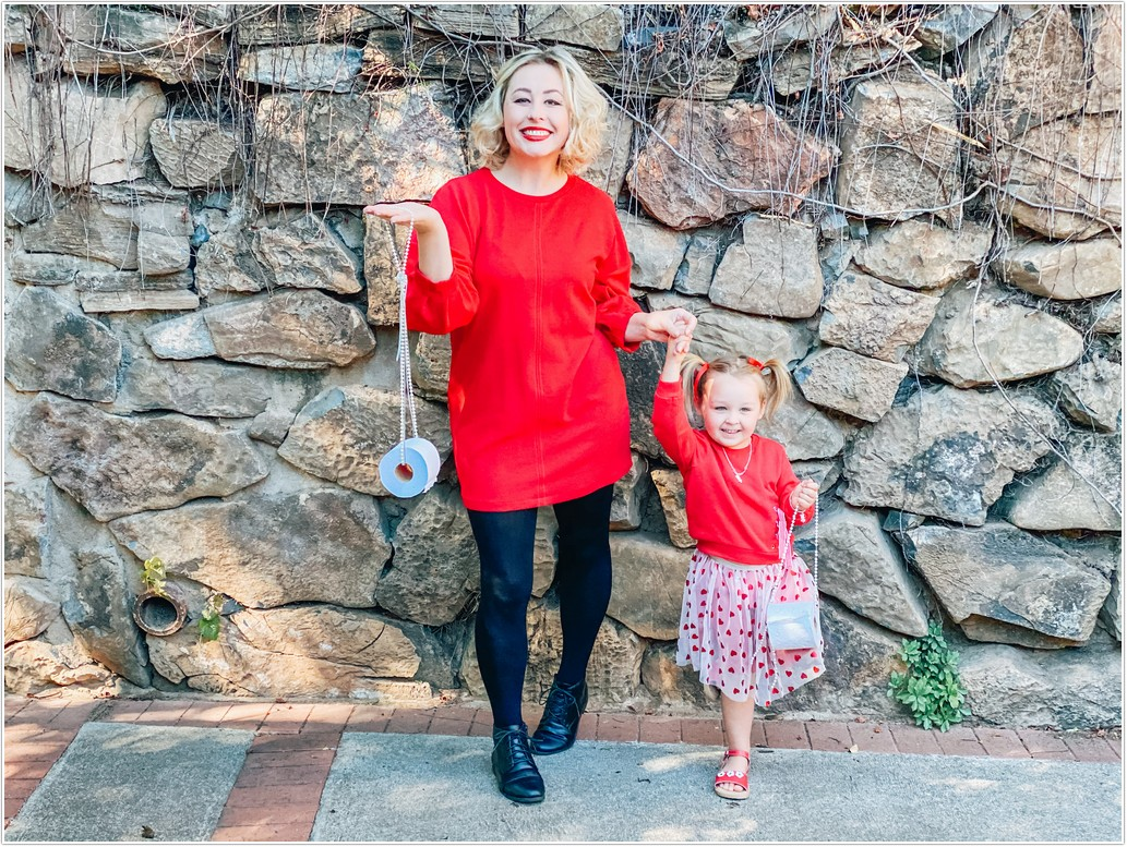 mom and toddler girl wearing matching red dresses posing with toilet paper handbags for the west pack toiletpaper challenge