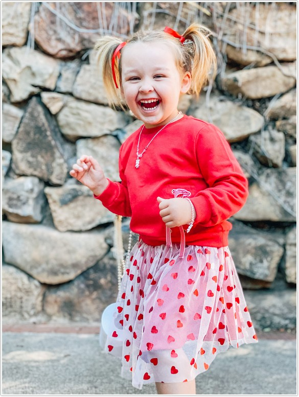 little girl wearing red sweater and skirt laughing at the camera with her toilet roll handbag for the west pack toiletpaper challenge