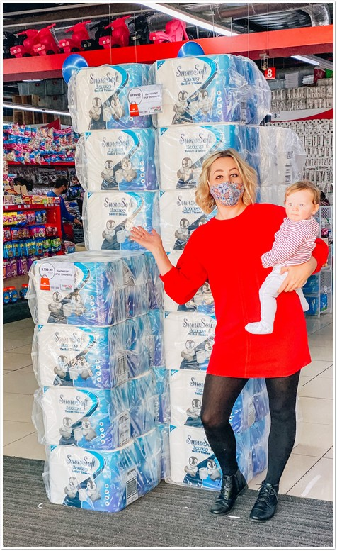 mom wearing red dress pointing to toilet paper display in west pack lifestyle store with baby boy on her hip part of the toilet paper challenge